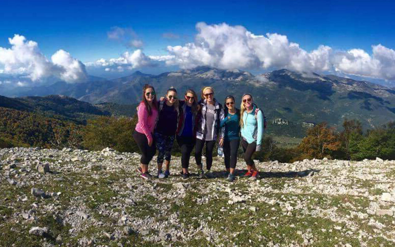 Assumption students pose before mountains on the outskirts of Rome.