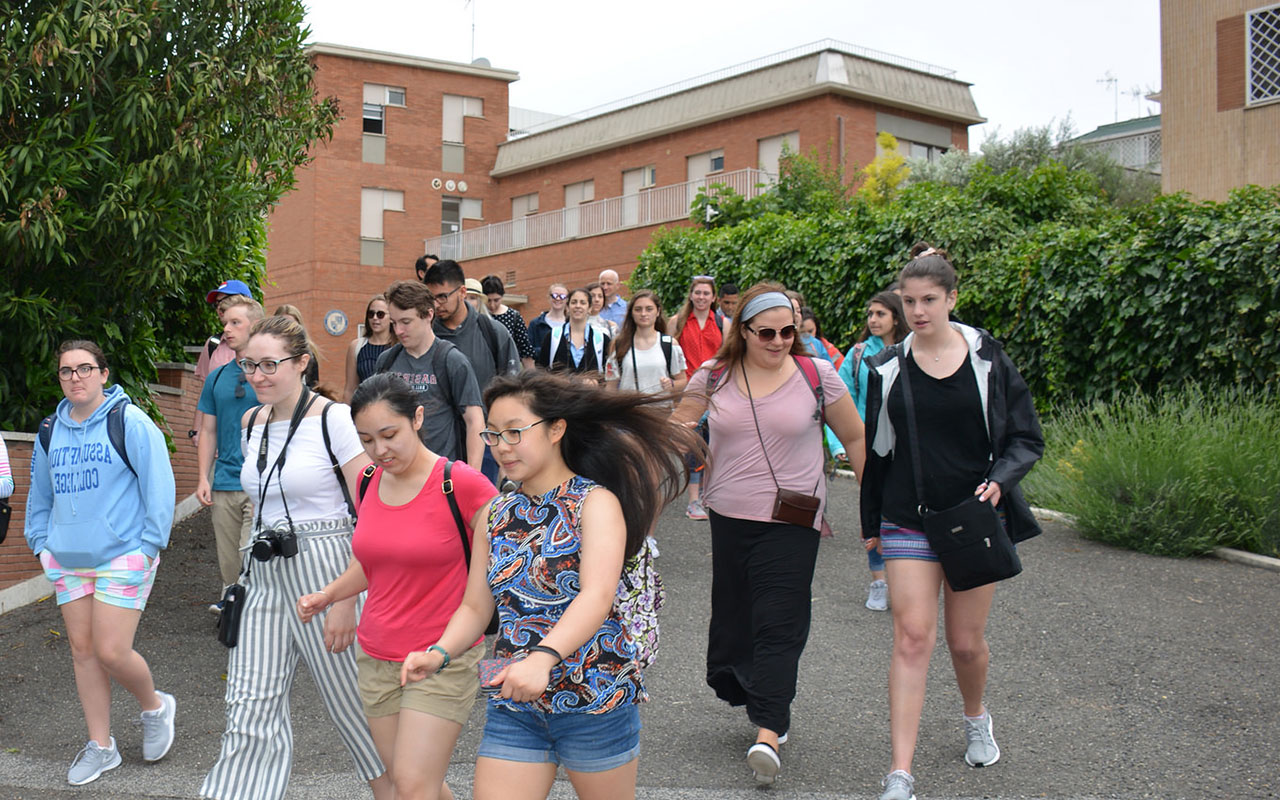 Assumption students walking down the driveway that leads to the College's campus in Rome.