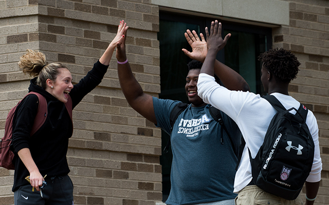 students high-fiving