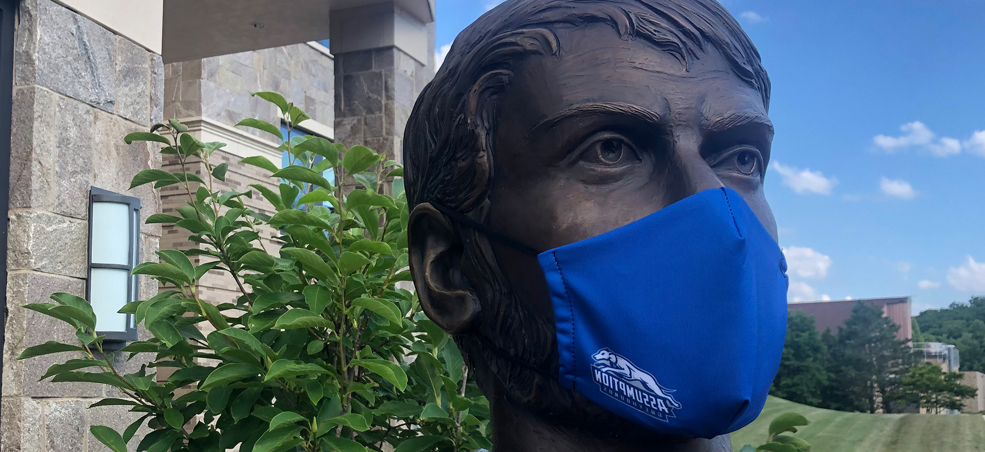Photo of St. Augustine wearing an Assumption blue face mask outside of the Tsotsis Family Academic Center.
